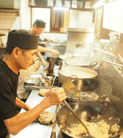 キッチンでチャーハンを調理するスタッフ